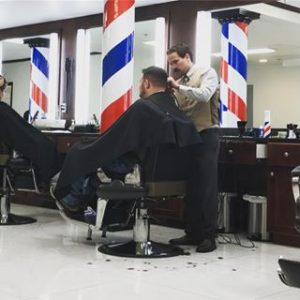 a barber performing men's haircuts at the barber shop