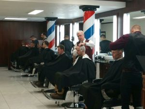 men's haircuts being performed by a barber